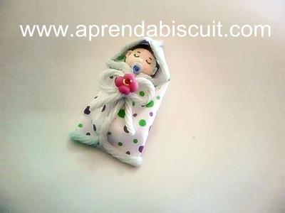 Bebê em biscuit no saquinho de pano para lembrancinha